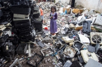 A young girl stands near stacks of used electronics at the electronic waste shelter in Jombang, East Java.